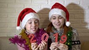 Dos niñas son que sientan y que juegan los cuadros rojos 2019 en los sombreros de Papá Noel en el sofá en un fondo blanco Retrato almacen de metraje de vídeo