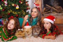 Dos niñas sonrientes hermosas que llevan una Navidad visten, abrazando sus gatos, la muchacha rizada con un lazo rojo en ella Imagenes de archivo