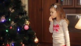 Dos niñas sonrientes que adornan decoraciones de la Navidad en árbol del Año Nuevo en casa Árbol de navidad con el abeto-cono nue almacen de metraje de vídeo