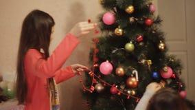 Dos niñas sonrientes que adornan decoraciones de la Navidad en árbol del Año Nuevo en casa Árbol de navidad con el abeto-cono nue almacen de video