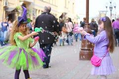 Dos niñas soplan muchas burbujas de jabón en la calle Foto de archivo libre de regalías