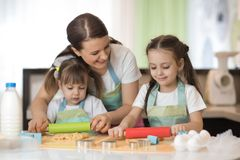 Dos niñas y su mamá hermosa en delantales son que juegan y de risas mientras que ruedan la pasta en la cocina Imagen de archivo