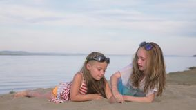 Dos niños adolescentes se están sentando en la playa almacen de video
