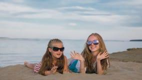 Dos niños adolescentes se están sentando en la playa imagenes de archivo