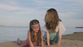 Dos niños adolescentes se están sentando en la playa metrajes