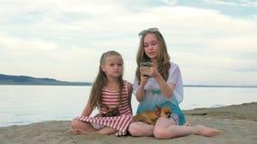 Dos niños adolescentes se están sentando en la playa en teléfono metrajes