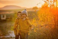 Dos niños adorables, divirtiéndose en la puesta del sol, haciendo caras divertidas Foto de archivo