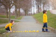 Dos niños adorables, hermanos del muchacho, jugando en parque con caucho foto de archivo libre de regalías