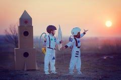Dos niños adorables, jugando en parque en puesta del sol, se vistieron como a Fotografía de archivo