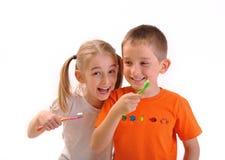 Dos niños aplican sus dientes con brocha aislados en blanco Imagen de archivo libre de regalías