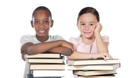 Dos niños apoyados en una pila de libros Foto de archivo libre de regalías