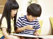 Dos niños asiáticos que juegan con una lupa en casa Fotografía de archivo