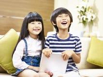 Dos niños asiáticos que se sientan en la risa del sofá Imágenes de archivo libres de regalías
