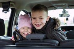 Dos niños bastante pequeños muchacho y muchacha en un interior del coche Imagenes de archivo