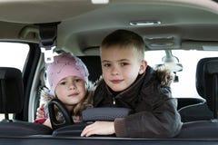 Dos niños bastante pequeños muchacho y muchacha en un interior del coche Foto de archivo