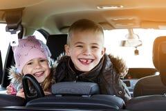 Dos niños bastante pequeños muchacho y muchacha en un interior del coche, trave Foto de archivo libre de regalías