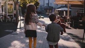 Dos niños caminan juntos, llevan a cabo las manos Cámara lenta Visión posterior Los pequeños niños exploran las calles viejas de  almacen de video