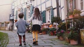 Dos niños caminan juntos a lo largo de edificios viejos La muchacha y el muchacho exploran la ciudad vieja alemana hermosa Unidad almacen de metraje de vídeo