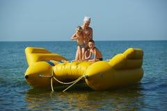 Dos niños con la mamá en la navegación del bote en el mar en verano Fotos de archivo