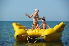 Dos niños con la mamá en la navegación del bote en el mar en verano Fotografía de archivo