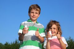 Dos niños con las pequeñas botellas del yogur Imagenes de archivo