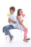 Dos niños con las piruletas Imagen de archivo libre de regalías