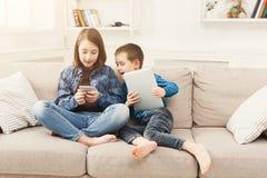 Dos niños con los artilugios en el sofá en casa Imagen de archivo libre de regalías