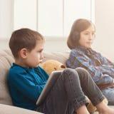 Dos niños con los artilugios en el sofá en casa Foto de archivo