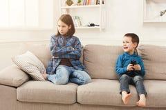 Dos niños con teledirigido en el sofá en casa Fotos de archivo libres de regalías