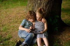 Dos niños de 7-8 años sientan la inclinación sobre la pantalla del ordenador portátil Fotos de archivo