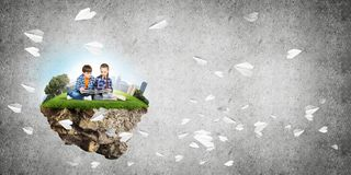 Dos niños de edad de escuela con el libro que exploran este gran mundo foto de archivo libre de regalías