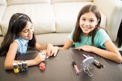 Dos niños de la diversión están jugando con los cosméticos Imagen de archivo libre de regalías