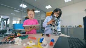 Dos niños de la escuela construyen un robot plástico en un laboratorio de la escuela Concepto de la educación técnica almacen de metraje de vídeo