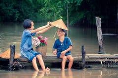 Dos niños de la muchacha que sientan y que juegan el agua junta en el puente de madera sobre el pantano, niños asiáticos que jueg imágenes de archivo libres de regalías
