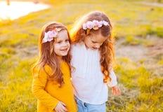 Dos niños de las hermanas en la puesta del sol al aire libre Imagen de archivo libre de regalías