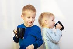 Dos niños de los muchachos que beben la bebida de las tazas Imagen de archivo libre de regalías