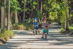 Dos niños de los niños pequeños que se divierten en la bici de la balanza en un camino tropical del país Imagenes de archivo