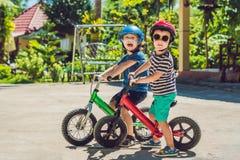 Dos niños de los niños pequeños que se divierten en la bici de la balanza en un camino tropical del país Foto de archivo libre de regalías