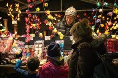 Dos ni?os emocionados con su abuela en un mercado de la Navidad fotos de archivo libres de regalías