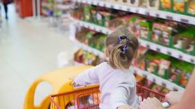 Dos niños en carro de la compra plástico dentro del mercado con el primer de la mamá almacen de video