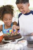 Dos niños en cocina con la torta de cumpleaños Imagenes de archivo