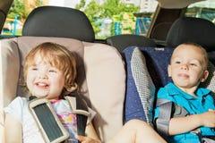 Dos niños en el asiento trasero en asiento de la seguridad del niño Imagenes de archivo