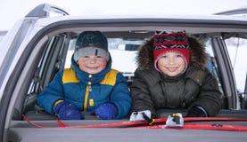 Dos niños en el coche que un feliz invierno dispara Fotos de archivo libres de regalías