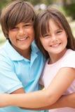 Dos niños en el parque que se da el abrazo imagenes de archivo