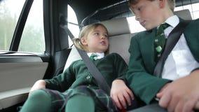 Dos niños en el uniforme que es conducido a la escuela almacen de video