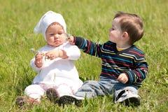Dos niños en la hierba Fotografía de archivo libre de regalías