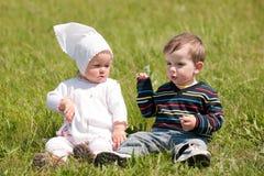Dos niños en la hierba verde Imagen de archivo