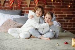 Dos niños en los pijamas que se sientan en los regalos de la Navidad de la cama que esperan para Imagenes de archivo