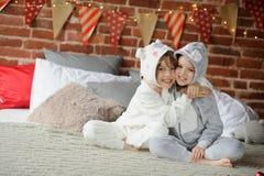 Dos niños en los pijamas que se sientan en los regalos de la Navidad de la cama que esperan para Foto de archivo libre de regalías
