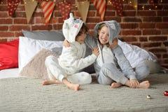Dos niños en los pijamas que se sientan en los regalos de la Navidad de la cama que esperan para Fotografía de archivo libre de regalías